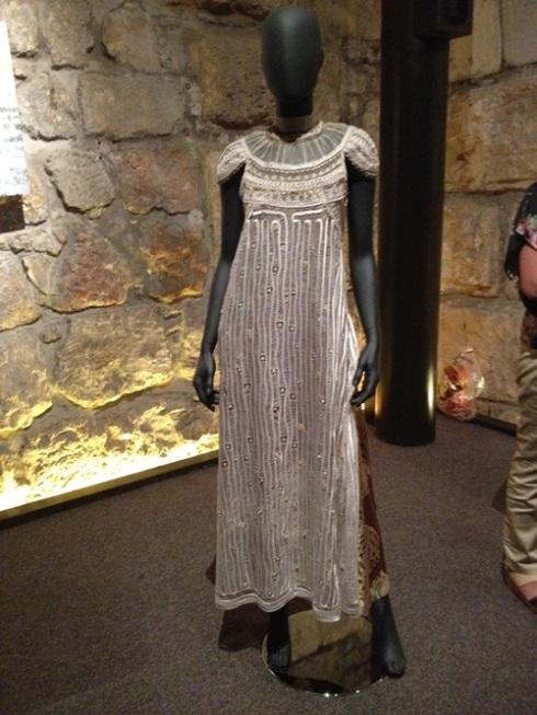הדגם של תמר שבמקור נלבש על ידי קרן מור, על רקע הקיר באולם האבירים.