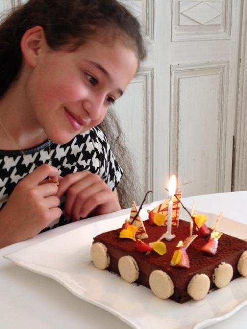 יעל המתוקה מתבוננת בעוגה שהוכנה עבורה במסעדת מוסקוני בלוקסמבורג